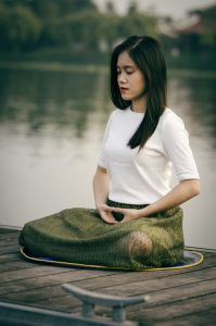 A woman sit by the river breathing