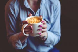 Ruke drže šolju sa toplom kafom