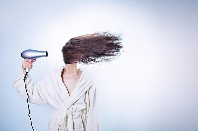 Žena suši kosu fenom